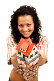 House in hand. Attractive young woman offering a miniature house Stock Image