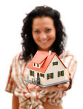 House in hand. Attractive young woman offering a miniature house Stock Photography
