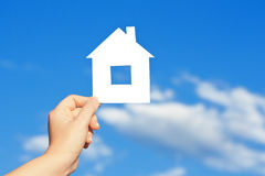 House in the hand against the blue sky Stock Photos