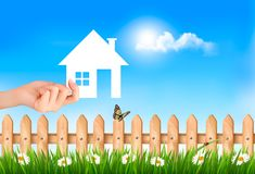 The house in hand on green natural background. Royalty Free Stock Image