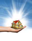 House in hand over blue sky Stock Images