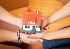 House in hands. Model house in hand of a couple, boxes in the background Royalty Free Stock Images