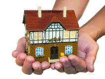House in hands. European style house in woman's hands. White background Royalty Free Stock Image