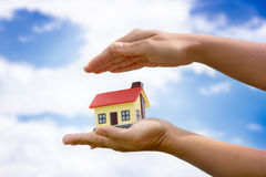 The house in hands on blue sky Royalty Free Stock Images