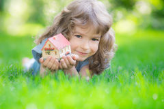House. Happy child holding model house in hands. Kid lying on green grass in spring park. New home concept Royalty Free Stock Photos