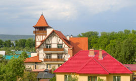 The house has a red roof and a tower. Stock Image