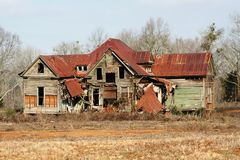 House haunting. Old house in field with tin roof Stock Photos
