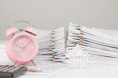 House have blur old pink alarm clock as background. House on finance account have blur old pink alarm clock and calculator with pencil and pile overload Stock Photos