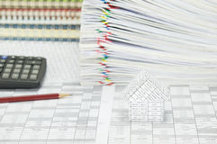 House have blur stack paperwork and notebook as background. House on finance account have blur pencil with calculator and pile paperwork of report with colorful Stock Image