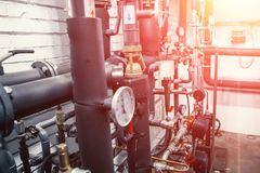 House heating system with many steel pipes, manometers and metal tubes. Selective focus with light effect royalty free stock photography