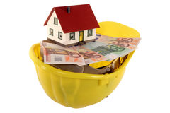 House on a helmet. A model of a building is on a helmet with Euro notes on it royalty free stock photography