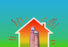 House with high heat loss illustration and couple of fingers. House with high heat loss illustration where two fingers inside on green background Royalty Free Stock Images