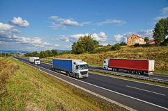 House of highway in a rural landscape, three trucks on the road Royalty Free Stock Photography