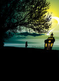 House on the Hill. An illustrative image of a house on a hill set against a moonlight sky. A silhouetted figure walks on a sloping horizon with a large tree. Low Stock Image