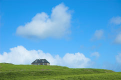 House on the Hill. Farm cottage peaking over brow of green hill with blue sky and clouds, Isle of Eigg, Scotland Stock Images