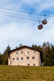 House on the hill and mountain gondola lift. Passenger cabin lift and house on a green hill in mountain. Blu sky background. Some trees in the woods. Location Royalty Free Stock Image