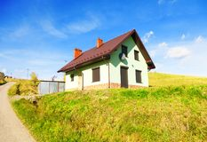 House, hills, field, path and sky royalty free stock photography