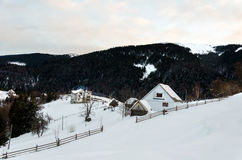 House on a hillside covered with snow and green trees on the sid royalty free stock photo