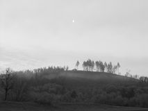 House on Hilltop with Half Moon. Black and white photo of house on hilltop with trees and half moon above it Stock Photo