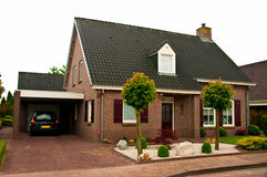 House in Holland. A typical suburban private house in Holland. Red brick building facade with car parked on the driveway stock photography