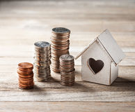 House Home Coin Stacks Business. A house with a heart and stacks of american coins on a rustic wood background stock photos