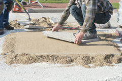 House or Home Improvement, Laying Stone Patio Landscaping. A worker is laying stone for patio landscaping. The type of stone is flagstone which has a natural royalty free stock image