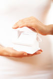 The house in human hands. Female hands holding saving small house with roof Stock Images