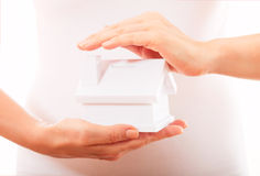 The house in human hands. Female hands holding saving small house with roof Royalty Free Stock Photo