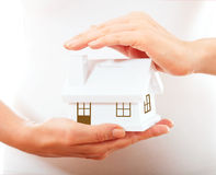 The house in human hands. Female hands holding saving small house with roof Royalty Free Stock Images