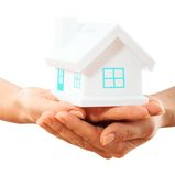 The house in human hands. Female hands holding saving small house with roof Stock Photos