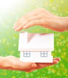 The house in human hands. Female hands holding saving small house with roof Royalty Free Stock Image