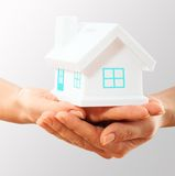 The house in human hands. Female hands holding saving small house with roof Royalty Free Stock Photography