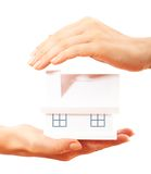 The house in human hands. Female hands holding saving small house with roof Stock Photo