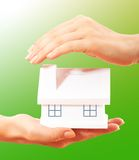 The house in human hands. Female hands holding saving small house with roof Stock Image