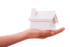 The house in human hands. Female hands holding saving small house with roof. Isolated over white background Royalty Free Stock Image