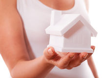 The house in human hands. Female hands holding saving small house with roof. Isolated over white background Royalty Free Stock Photo