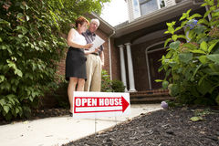 House Hunting. Mature couple standing in front of a home with an Open House sign looking at documents Stock Images