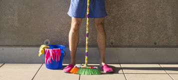 House husband in pink slippers cleaning the floor Royalty Free Stock Photo