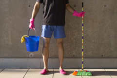 House husband in pink slippers cleaning the floor Stock Photos