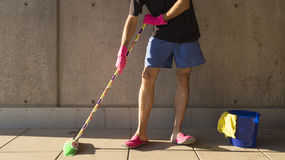 House husband in pink slippers cleaning the floor Stock Images
