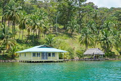 House and hut over water Caribbean coast of Panama. House and hut over the water with coconut palm trees on the land, Caribbean coast of Panama, Bocas del Toro royalty free stock images