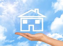 House icon on hand. Background of sky , clouds and Stock Photos