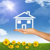 House icon on hand. Background of sky, clouds and stock photos