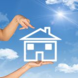 House icon on hand. Background of sky, clouds and royalty free stock photos