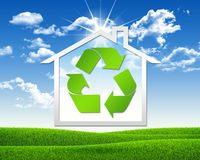 House icon with symbol recycling. Green grass and blue sky as backdrop Royalty Free Stock Images