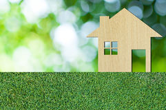 House icon from wooden on grass texture nature background as symbol of mortgage royalty free stock image