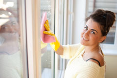 House improvement. Pretty woman wash windows in glove Stock Photos