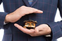 House insurance concept with agent hands. House insurance concept with close-up of agent hands holding miniature home model for protection Royalty Free Stock Photo