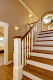 House interior. Hallway with wooden staircase and white railings. Royalty Free Stock Photo