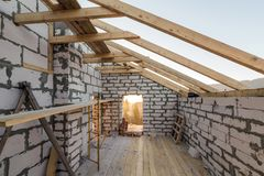 House interior under construction and renovation. Energy saving walls of hollow foam insulation blocks and bricks, ceiling beams. And roof frame stock photo
